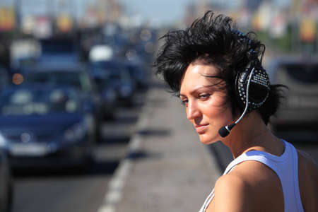 girl in headphone set on highway middle, Has looked back photo