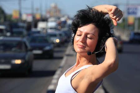 dancing girl in headphone set on highway middle photo