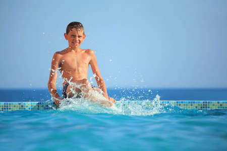 teenager boy splashes feet water in pool against sea Stock Photo - 7835945