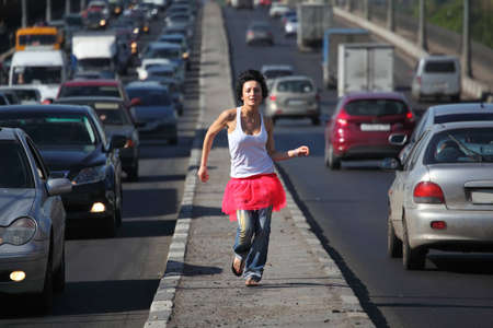 girl in pink skirt runs on highway middle photo