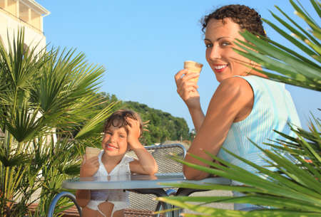 little girl and young woman eat ice-cream near palm trees on resort photo