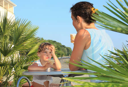 little girl and young woman eat ice-cream near palm trees on resort, Looking against each other Stock Photo - 9758480