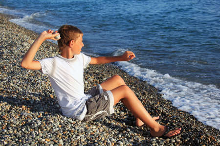 waves  pebble: sitting boy throws stone in sea