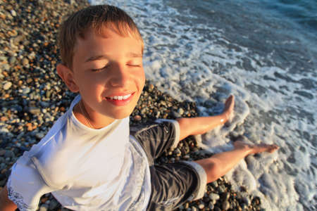 sitting teenager boy on stone seacoast, closed eyes, wets feet in water photo