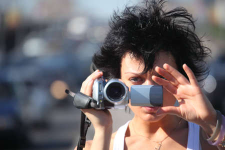 Portrait of girl with videocamera on highway photo