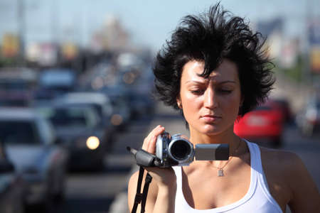girl with videocamera on highway photo