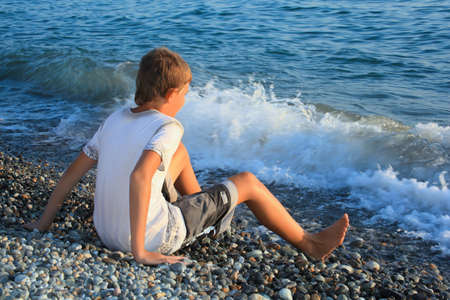 sitting teenager boy on stone seacoast, wets feet in water, sitting by back photo