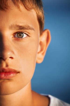 teen boys: surprised teenager boy against sea, half of face