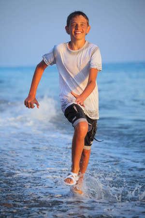 Teenager Boy läuft in der nassen Kleidung auf Strand