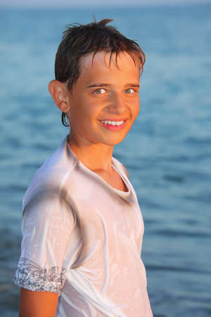 teenager boy in wet clothes on seacoast photo