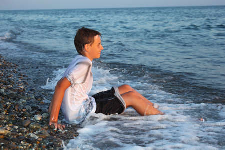 shingle beach: sitting teenager boy in wet clothes on stone seacoast