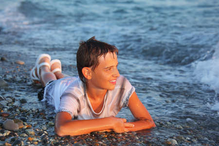 wet clothes: teenager boy  in wet clothes lying on stones on seacoast