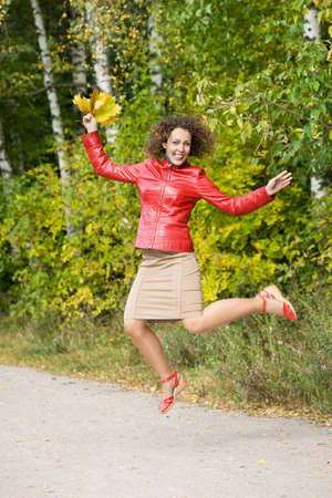 young woman with leaves in hands in jump in wood in autumn photo