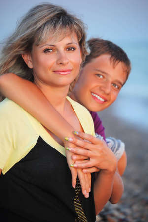 smiling boy embraces young woman on beach in evening Stock Photo - 7836841