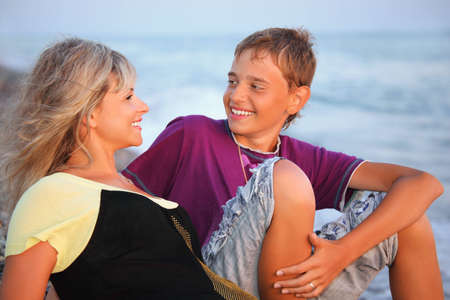 smiling boy and young woman on beach in evening, Looking against each other Stock Photo - 7836144