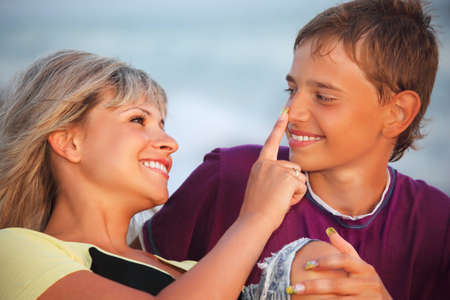 young woman touches with finger nose of smiling boy in evening, Looking against each other photo
