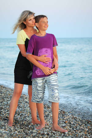 mom and son: young woman embraces smiling boy on beach in evening