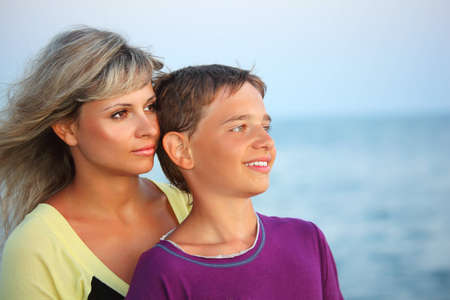 smiling boy and young woman on beach in evening, Looking afar photo