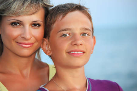 smiling boy and young woman on beach in evening photo