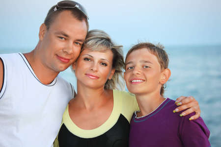 Happy family with smiling boy on beach in evening photo