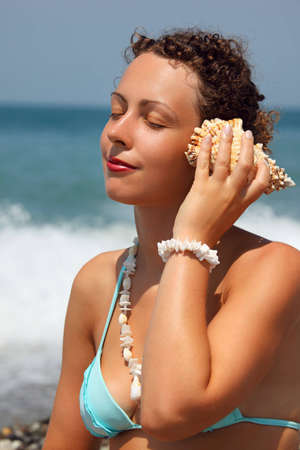 leant: beautiful woman has leant seashell bowl to an ear on seacoast Stock Photo