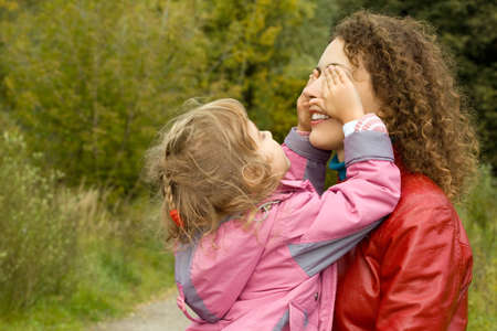 closes eyes: young woman and little girl playing in garden, girl closes eyes to mother Stock Photo