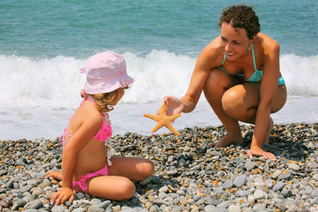 young woman gives starfish to little girl on stony beach photo