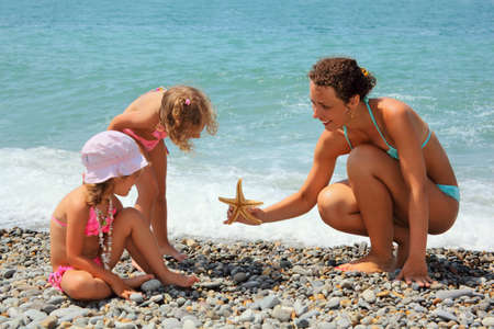 young woman gives starfish to two little girls on stony beach photo