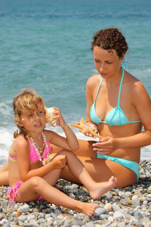 beautiful woman with pretty little girl has leant seashell bowl to an ear on stone seacoast photo