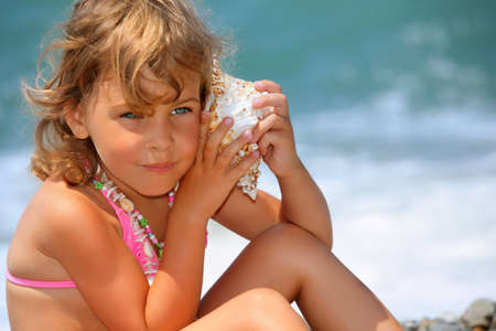 leant: pretty little girl has leant seashell bowl to an ear on seacoast
