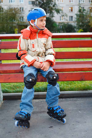 boy in the rollers sitting on a bench photo