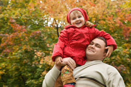 overweight people: little girl sits on shoulder at man In park in autumn Stock Photo