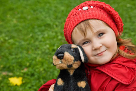 little girl with a toy dog in park photo