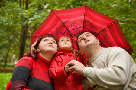 Married couple and  little girl with umbrella in park photo