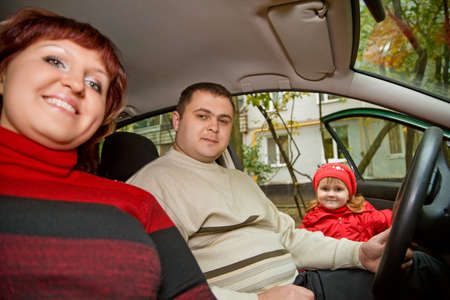 Married couple and  little girl sit in car near a building photo