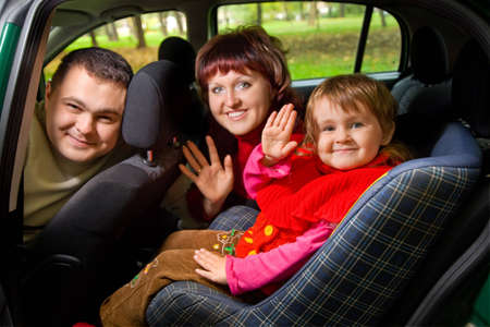Married couple and  little girl  Greeting to wave hands in car in park  photo