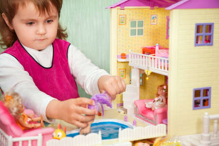 little girl washes a doll in pool of toy house   photo
