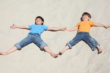 Two children lying nearby on sand photo