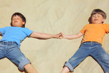 two boys lie on sand with closed eyes photo