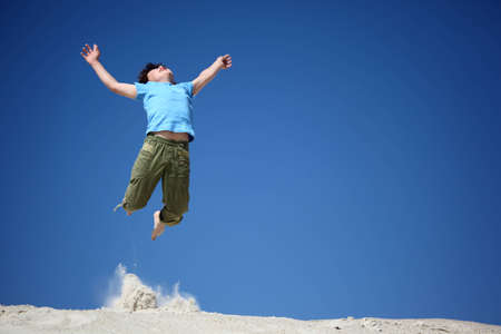 lifted hands: boy jumps on sand with  lifted hands