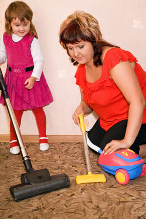 Little Girl and woman vacuum a carpet photo