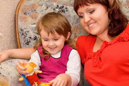 little girl and woman play a toy in a cosy room photo