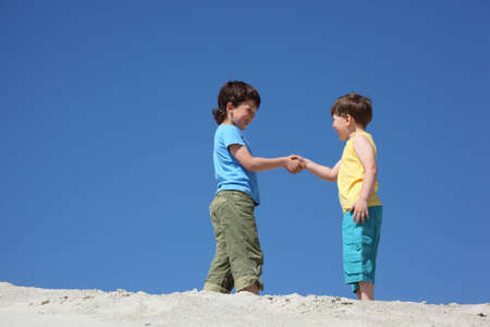 greet: Two boys greet on sand