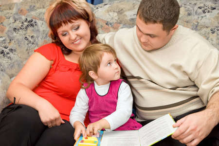 Married couple and  little girl read  book in a cosy room photo