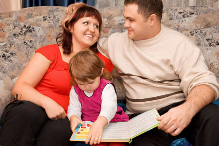 obese child: Married couple and  little girl read  book in a cosy room