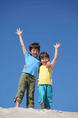lifted hands: Two boys stand on sand and  lifted hands in greeting Stock Photo