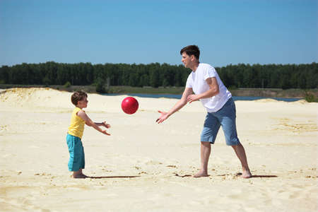 father and son throw each other ball on sand photo