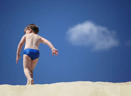 little boy swimming: boy going on sand,  rear view, focus on hand