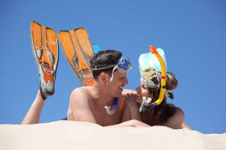 young pair in fins and underwater masks lies on sand Stock Photo - 7836213