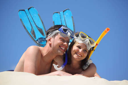 young pair in fins and underwater masks lies on sand Stock Photo - 7836259